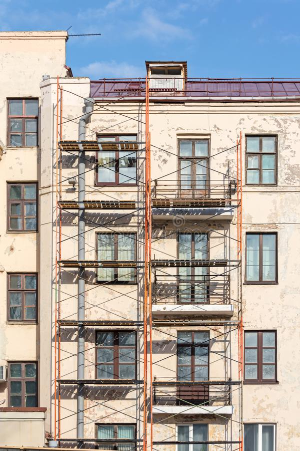 Renovation of old residential building with construction scaffolding near wall stock photo
