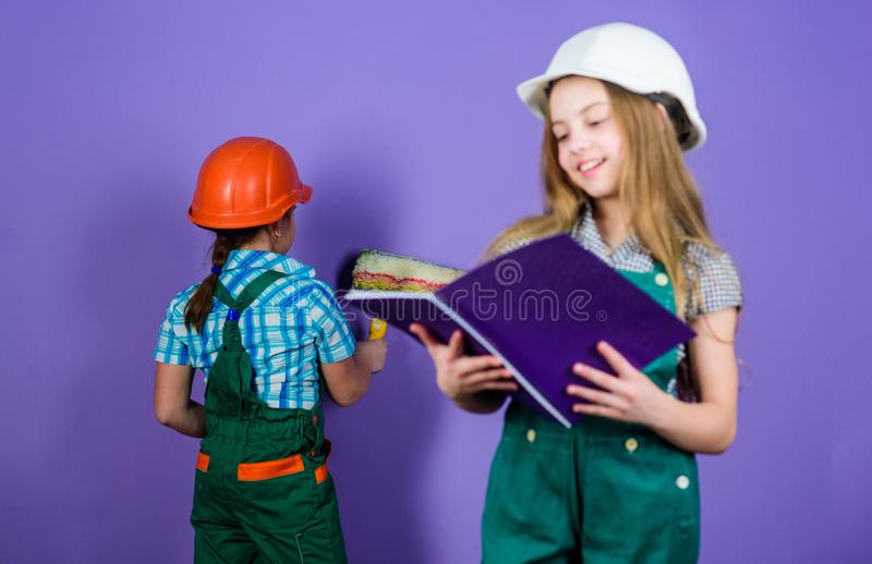 Renovation team. Kids girls planning renovation. Repaint walls. Move in new apartment. Children sisters run renovation royalty free stock photography