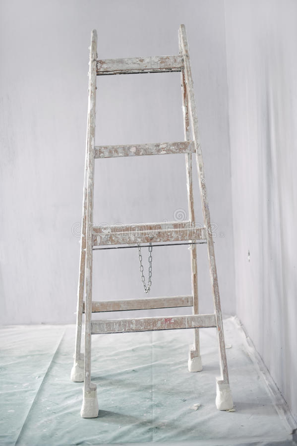 Renovation of a wall in empty room with ladder stock photography