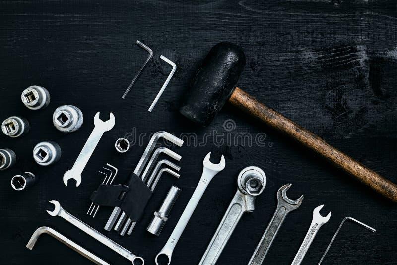 Renovera en bil En uppsättning av reparationshjälpmedel förhäxer tangenter, en hammare och en skruvmejsel på en svart träbakgrund arkivbild