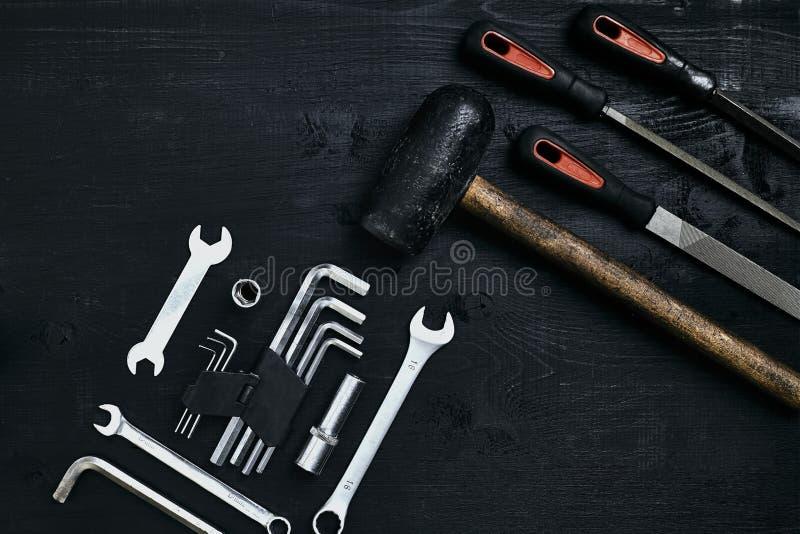 Renovera en bil En uppsättning av reparationshjälpmedel förhäxer tangenter, en hammare och en skruvmejsel på en svart träbakgrund fotografering för bildbyråer