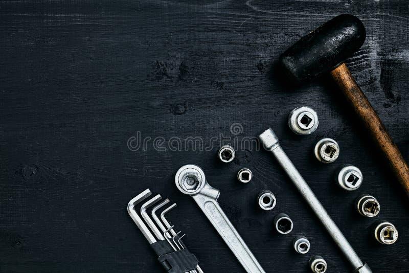 Renovera en bil En uppsättning av reparationshjälpmedel förhäxer tangenter, en hammare och en skruvmejsel på en svart träbakgrund arkivfoton