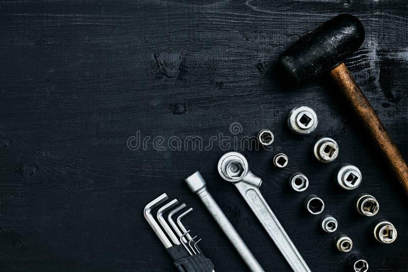 Renovera en bil En uppsättning av reparationshjälpmedel förhäxer tangenter, en hammare och en skruvmejsel på en svart träbakgrund royaltyfri fotografi