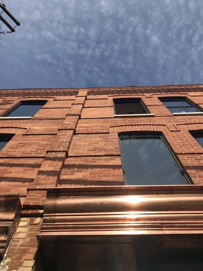 Renoverad brun tegelsten går upp med blå himmel och koppardetaljer royaltyfria bilder