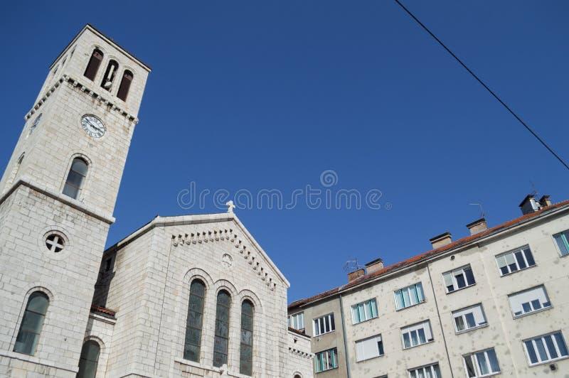 Renoverade lägenheter med kulhål och kyrka i Sarajevo royaltyfria bilder