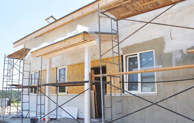 Renovering av det lantliga huset med att rappa och att måla i yttre husvägg för vit färg royaltyfri foto