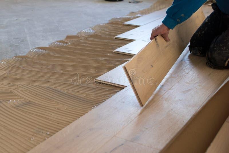 Renovering av en lägenhet, den kompetenta arbetaren använder en plast- hammare arkivbilder