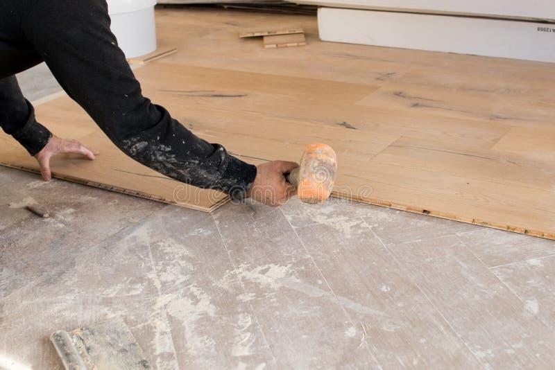 Renovering av en lägenhet, den kompetenta arbetaren använder en plast- hammare fotografering för bildbyråer