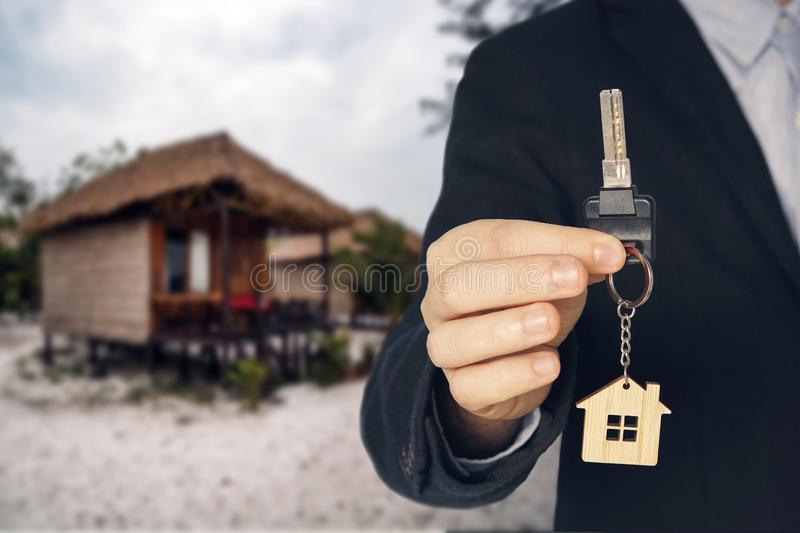Rent a Bungalow on the beach for a holiday. man buying new house. hand receiving house key. Close up hand holding house key stock images