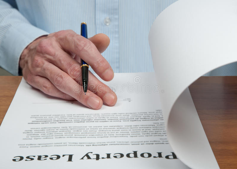 Rent Contract. Male businessmen is reading the property lease contract before signing it stock photography