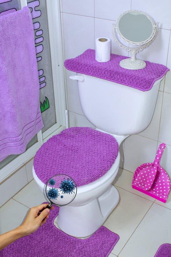Rent toalettrum, med ett förstoringsglas i hand Befruktning av antibacterial lokalvård i toaletten arkivbilder