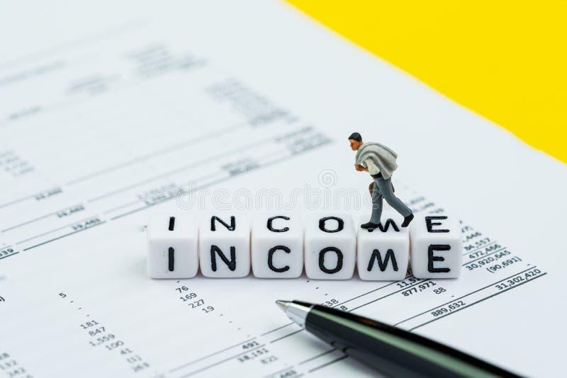 Renta, sueldo o concepto de los salarios, hombre de negocios miniatura del empleado de la oficina caminando en pequeños bloques d imagen de archivo libre de regalías
