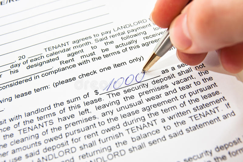 Rental agreement. Man's hand with gold pen writing 1000 (one thousand) dollars amount on a rental agreement printed on paper stock image