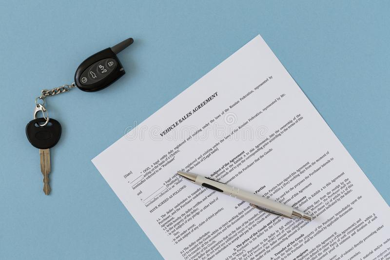Rental agreement for a car with contract, pen and keys. Concept of selling, renting and insuring a car. Flat lay composition stock image