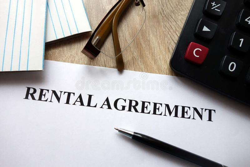 Rental agreement form. With pen, calculator and glasses on desk stock image