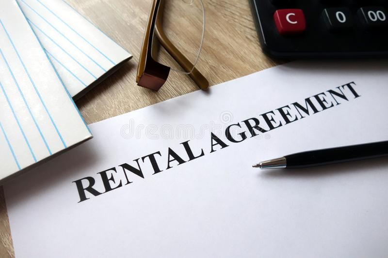 Rental agreement form. With pen, calculator and glasses on desk royalty free stock images