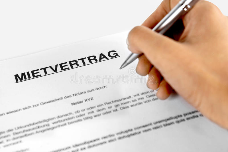 Rental agreement form with signing hand with the German Word Mietvertrag. Rental agreement form with signing hand - Concept with the German Word Mietvertrag royalty free stock photos