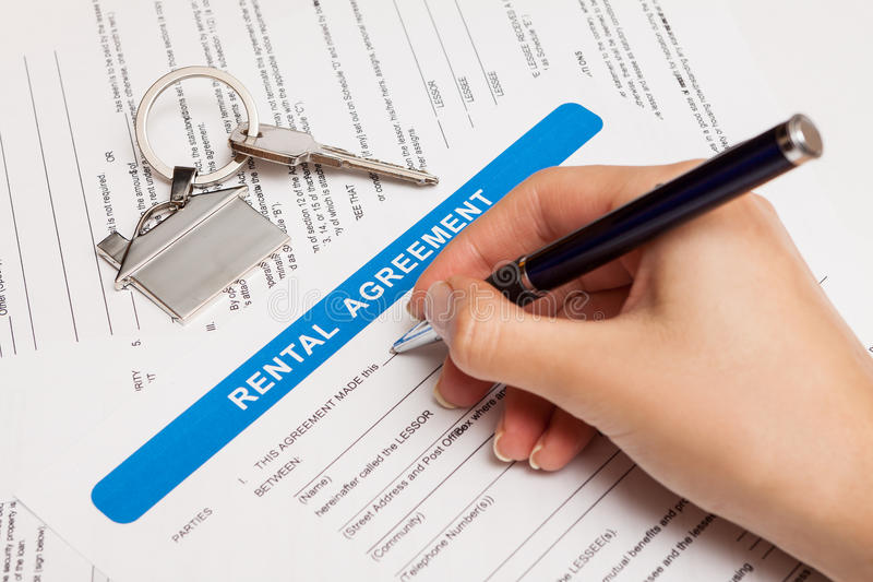 Rental agreement form. With signing hand and keys and pen stock photos