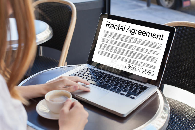Rental agreement. Rent a car or house, woman reading tenancy contract on the screen of laptop royalty free stock images