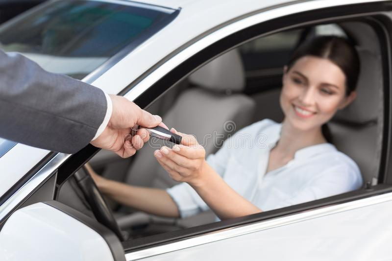 Man auto dealer offering car key to woman. Rental contract. Man auto dealer offering car key to woman royalty free stock image