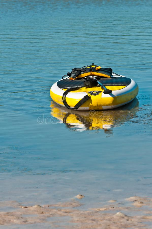 Rental paddle boat in backwater of the gulf of mexico. Front view, medium distance of an inflatable, yellow, rental, paddle boat and paddle, in backwater of a stock images