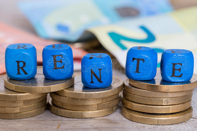 Rente in german pension letter cubes on coins concept. stock image
