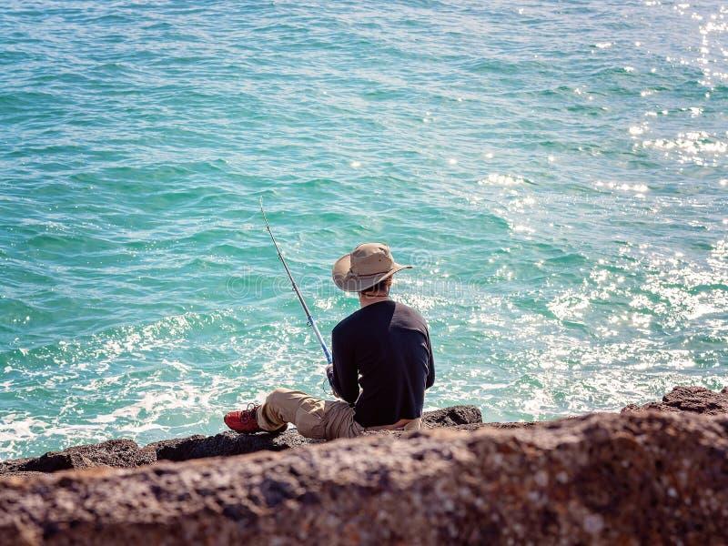 Rentner-m?nnliches Fischen von den Wellenbrecher-Felsen stockfotos