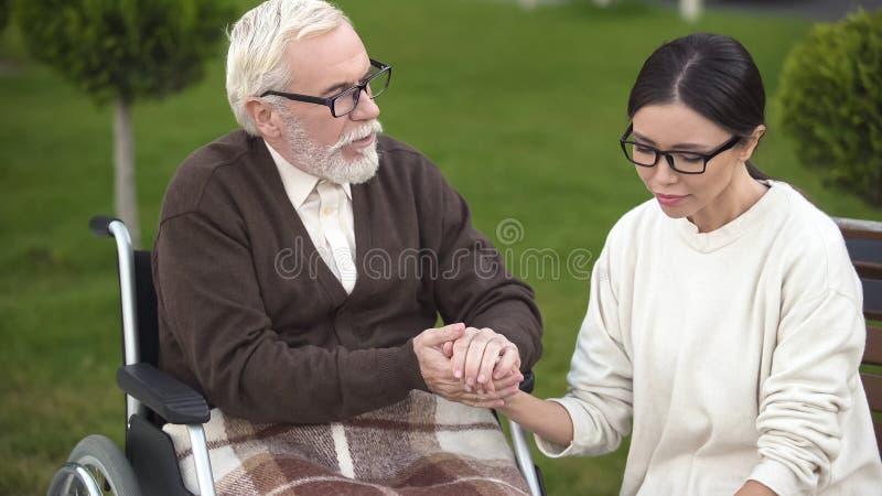 Renversement de consolation masculin plus âgé de dame avec le mauvais diagnostic, visite à la maison de repos photographie stock