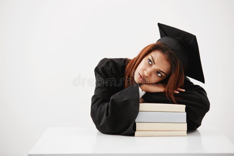 Renversement et fatigué d'étudier la fille africaine d'étudiant et le diplômé d'avenir s'étendant sur des livres pensant à la pro photo stock