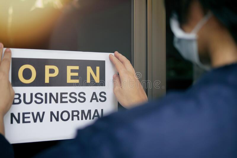 Reopening for business adapt to new normal in the novel Coronavirus COVID-19 pandemic. Rear view of business owner wearing medical. Mask placing open sign stock photography