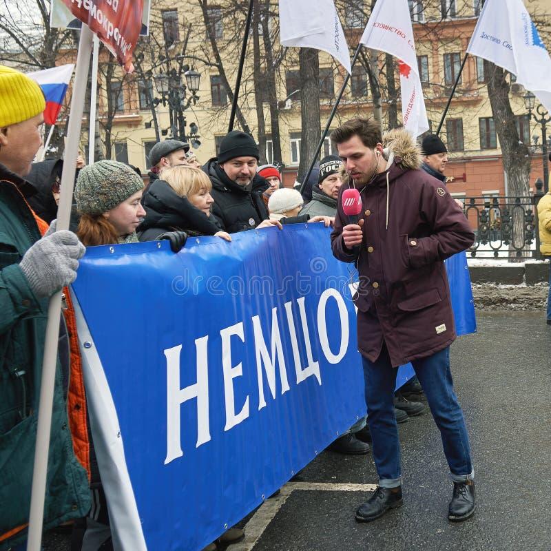 Repórter dos demonstradores de entrevista de Aleksei Korostelev do canal da chuva da tevê do russo que levam uma bandeira polític fotografia de stock royalty free