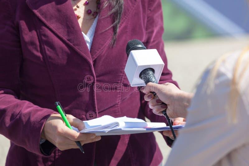 Repórter fêmea que guarda o microfone, mulher de entrevista imagem de stock