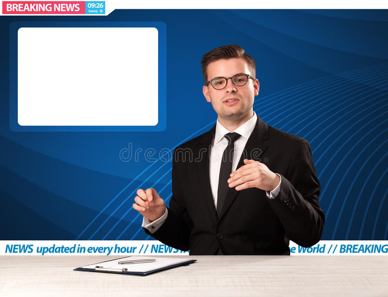 Repórter televisivo que diz notícias de última hora em sua sagacidade da mesa do estúdio foto de stock