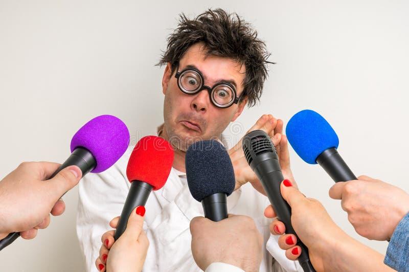 Repórteres que fazem a entrevista com cientista engraçado fotos de stock