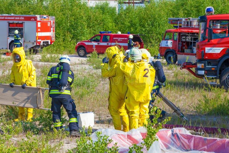 REPÚBLICA CHECA, PLZEN, 4 JUNY, 2014: Cuerpos de bomberos y equipos de la emergencia en trajes del hazmat fotos de archivo