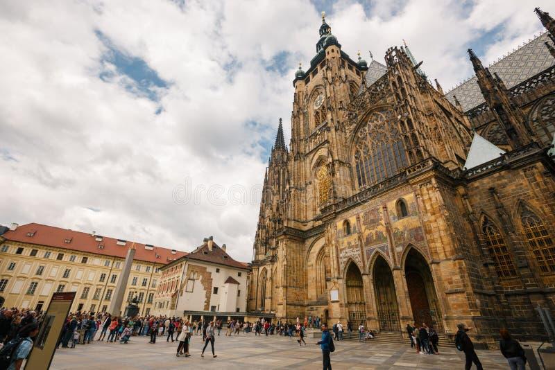 República Checa, Praga, o 25 de julho de 2017: Um quadrado com turistas aproxima a catedral gótico de St Vitus com o céu azul no  imagem de stock