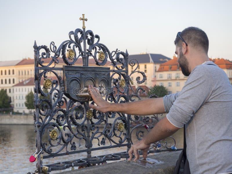 República Checa, Praga, o 8 de setembro de 2018: Turista do homem novo que toca no padre de queda Saint John de Nepomuk no plaq d fotos de stock royalty free