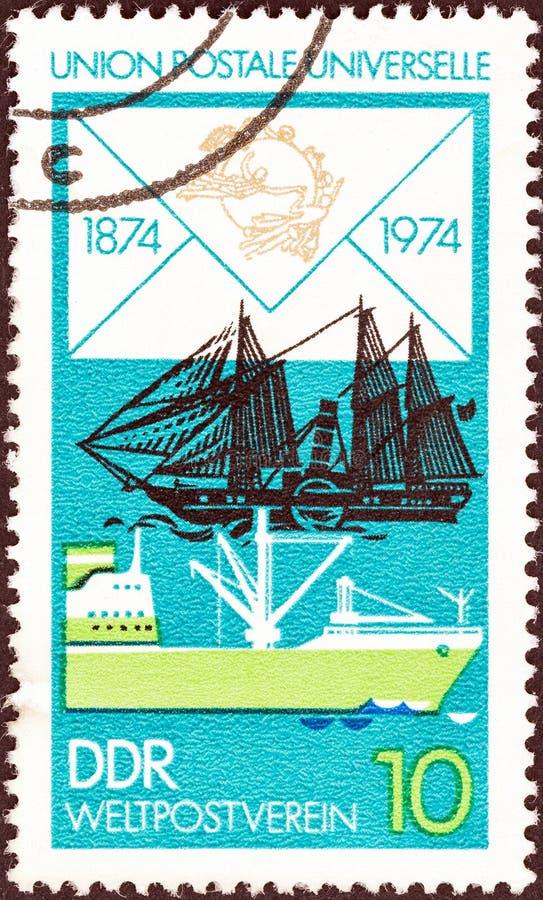 REPÚBLICA DEMOCRÁTICA ALEMÃ - CIRCA 1974: Um carimbo impresso na Alemanha mostra James Watt paddle steamer e Modern Freighter imagens de stock royalty free