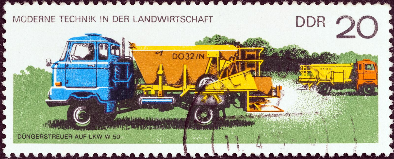 REPÚBLICA DEMOCRÁTICA ALEMANA - CIRCA 1977: Un sello impreso en Alemania muestra el esparcidor del fertilizante en el camión, cir imagen de archivo libre de regalías