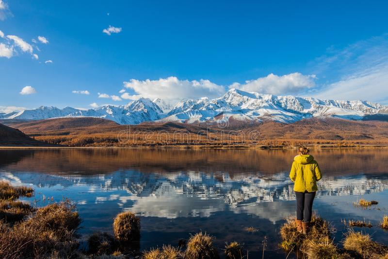 Rep?blica de Altai La muchacha es un turista al lado del lago de la montaña contra el contexto de picos nevosos y del taiga del a fotografía de archivo