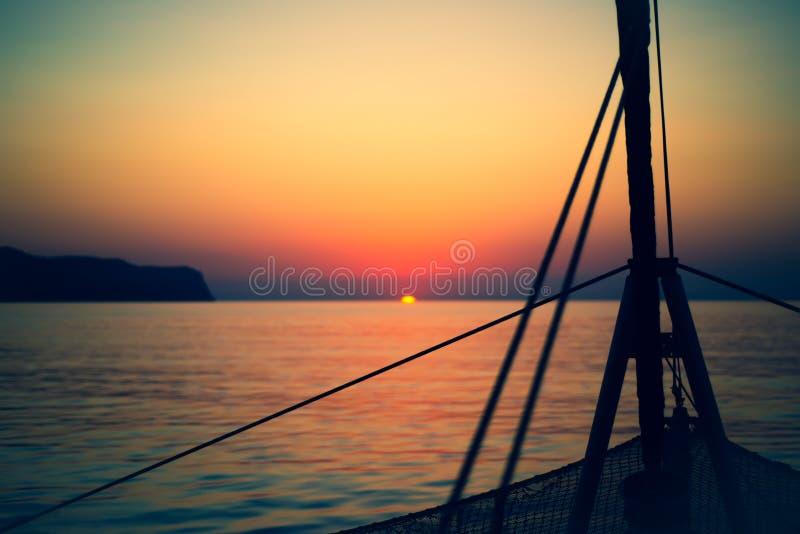 Rep på en segelbåt med soluppgång och öar i bakgrunden arkivbild