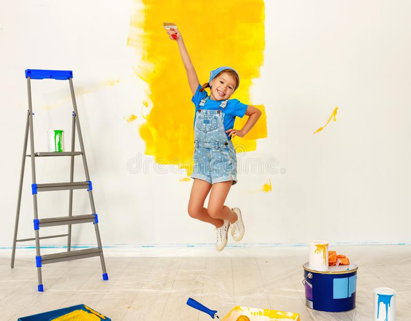 Repair in apartment. Happy child girl jumping paints wall. Repair in the apartment. Happy child girl jumpingpaints the wall with yellow paint stock photo