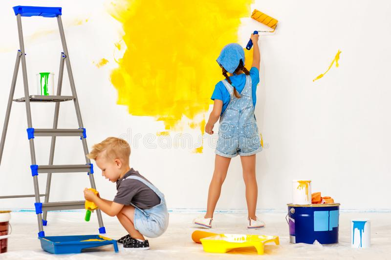 Repair in apartment. Happy children boy and girl paints wall. Repair in the apartment. Happy children boy and girl  paints the wall with yellow paint stock photos