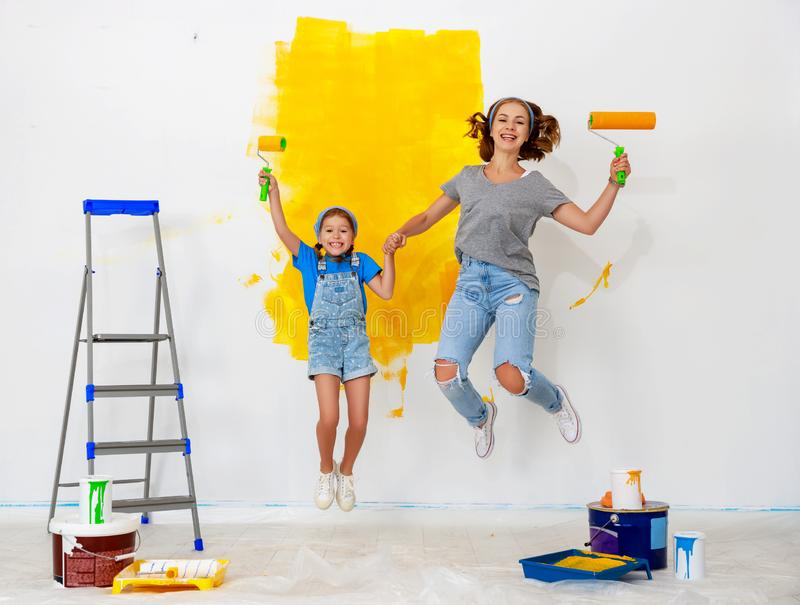 Repair in apartment. Happy family mother and child daughter jumping and paints wall royalty free stock photos