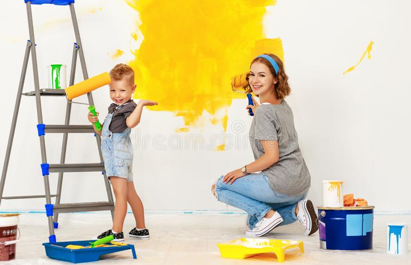 Repair in apartment. Happy family mother and child son paints wall royalty free stock photo