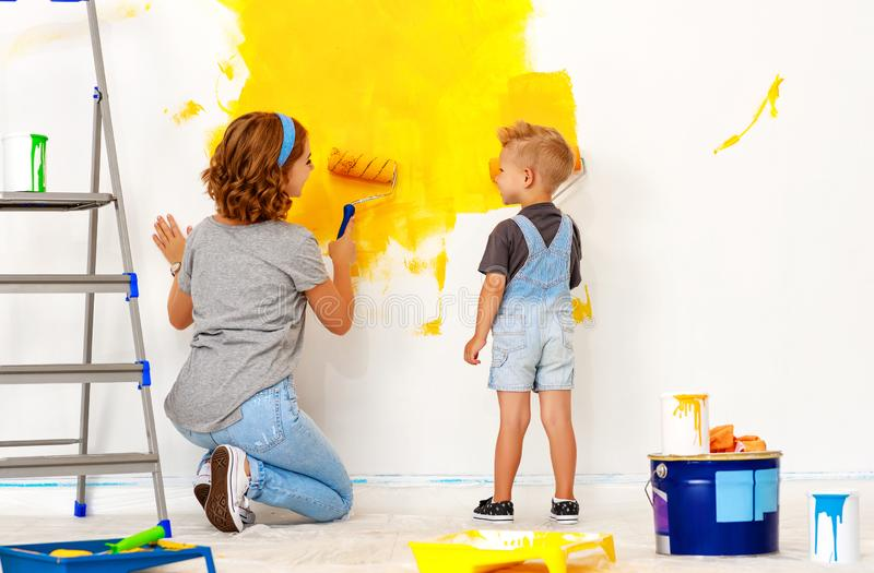 Repair in apartment. Happy family mother and child son paints wall. Repair in the apartment. Happy family mother and child son  paints the wall with yellow paint royalty free stock photos