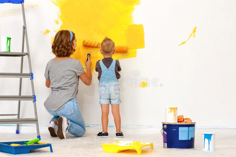 Repair in apartment. Happy family mother and child son paints wall. Repair in the apartment. Happy family mother and child son  paints the wall with yellow paint stock images