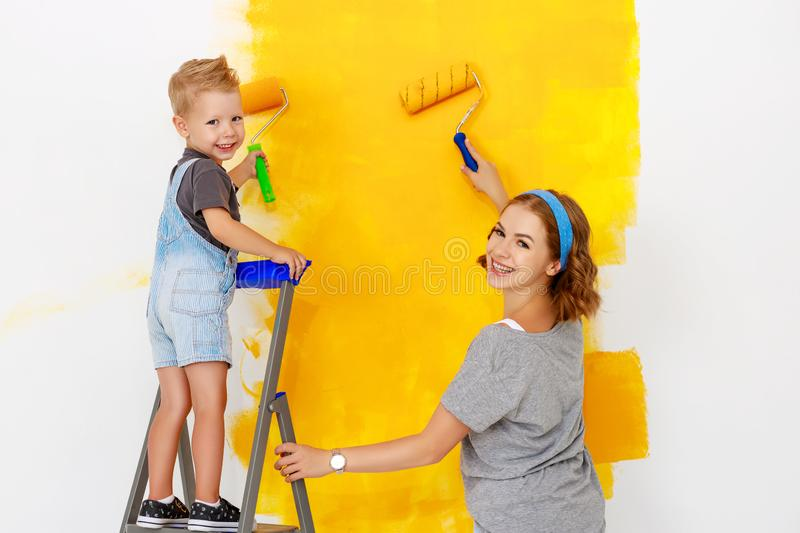 Repair in apartment. Happy family mother and child son paints wall. Repair in the apartment. Happy family mother and child son  paints the wall with yellow paint royalty free stock images