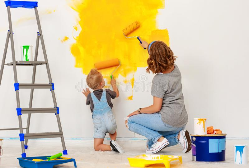 Repair in apartment. Happy family mother and child son paints wall. Repair in the apartment. Happy family mother and child son  paints the wall with yellow paint stock photography