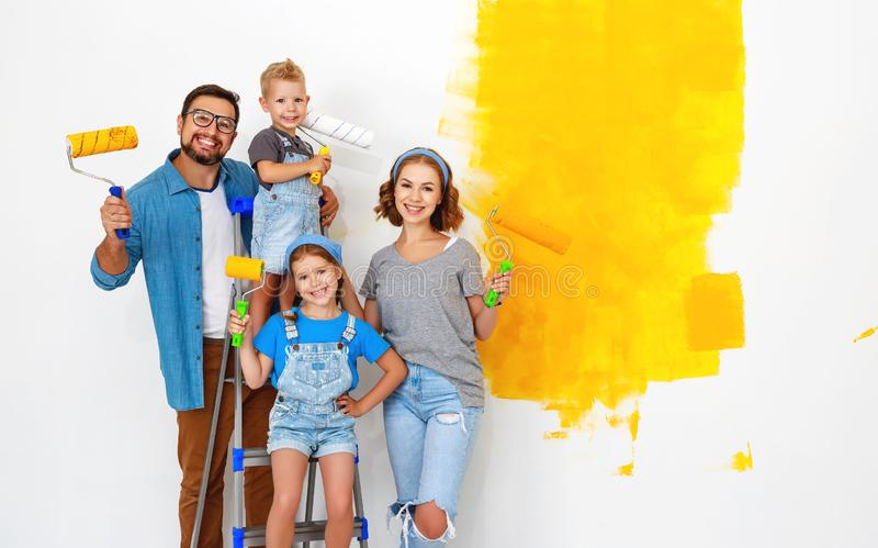 Repair in apartment. Happy family mother, father and children   paints wall. Repair in the apartment. Happy family mother, father  and children   paints the wall stock image